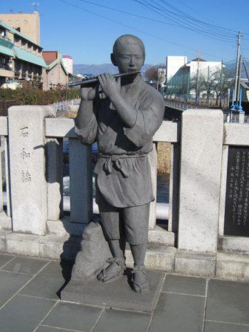 石和橋上の笛吹権三郎の像
