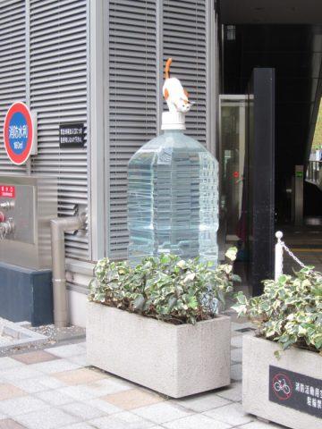 巨大なペットボトルに猫が乗っているオブジェ